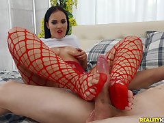 Jennifer Mendez dons dispirited red fishnets and gives a hot footjob to the fore sex